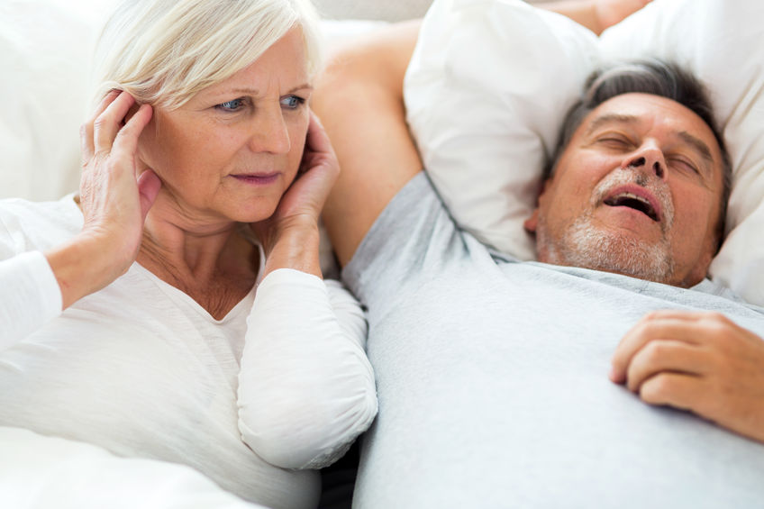 64799427 - senior man snoring and woman covering ears